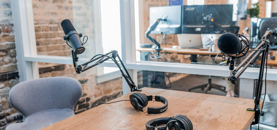 Podcast studio with two microphones and two headphones laying on a table