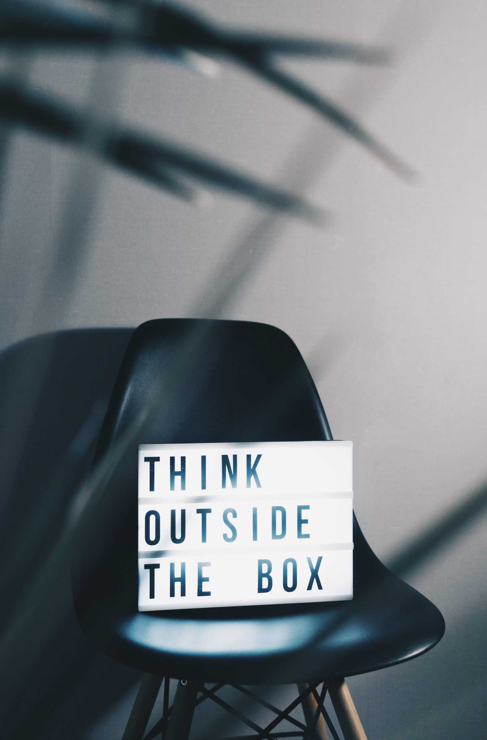 Sign sitting on a chair that says think outside the box